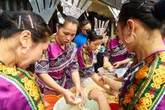 Le donne hanno vestito i costumi tradizionali che preparano i pastelli ed i dolci fotografie stock