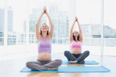Le donne incinte felici nella classe di yoga che si siede nel loto posano immagini stock