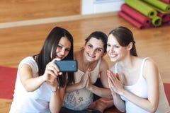 Le donne incinte sorridenti prendono le immagini di se stessi su uno smartphone nella palestra dopo un allenamento immagine stock libera da diritti