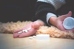 Le donne indicano dopo la presa della dose eccessiva della medicina con la bottiglia di pillole aperta Concetto della dose eccess immagine stock