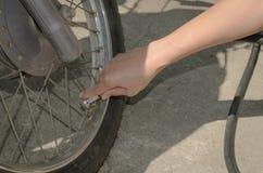 Le donne inscatolano l'aria di riempimento in una gomma del motociclo Fotografia Stock