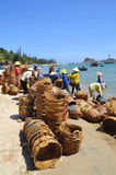Le donne locali stanno pulendo i loro canestri che sono stati usati per il trasporto dei pesci dalla barca al camion Fotografia Stock
