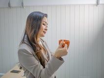 Le donne moderne di affari tengono la sua tazza o tazza di caffè fotografie stock