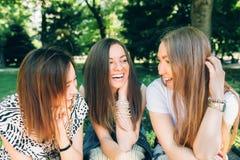 Le donne multirazziali del ritratto di stile di vita dell'estate godono del giorno piacevole Amici felici nel parco un giorno sol fotografia stock libera da diritti