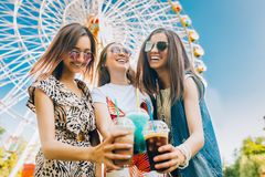 Le donne multirazziali del ritratto di stile di vita dell'estate godono del giorno piacevole, tenente i vetri dei frappé Parte an fotografia stock