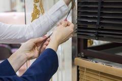 Le donne nel deposito scelgono i ciechi per le finestre immagini stock