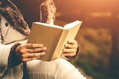 Le donne nell'inverno si siedono hanno letto il libro favorito nella festa immagine stock libera da diritti