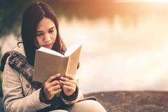 Le donne nell'inverno si siedono hanno letto il libro favorito nella festa immagine stock