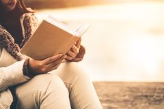 Le donne nell'inverno si siedono hanno letto il libro favorito nella festa fotografie stock libere da diritti