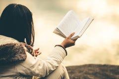 Le donne nell'inverno si siedono hanno letto il libro favorito nella festa fotografia stock libera da diritti