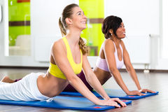Le donne nella palestra che fa l'yoga si esercitano per forma fisica Fotografia Stock