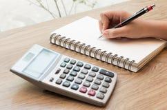Le donne passa la scrittura con la matita, il taccuino ed il calcolatore Immagini Stock Libere da Diritti