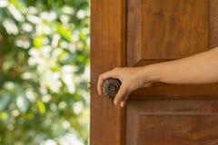 Le donne passano la manopola della porta aperta o aprono la porta fotografia stock