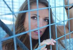 Le donne radrizza la ragazza della restrizione in recinto di griglia del metallo della prigione fotografie stock libere da diritti
