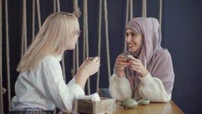 Le donne religiose ed etniche differenti di tradizioni, stanno sedendo insieme in caffè stock footage