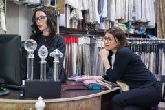 Le donne scelgono i tessuti per le tende e la tappezzeria della mobilia in nuova casa, esamina il monitor del computer, conversaz Fotografia Stock