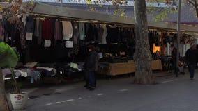 Le donne scelgono i vestiti nel mercato di strada stock footage