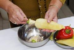 Le donne senior preparano e puliscono il pepe per cucinare immagini stock