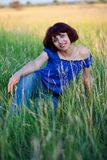 Le donne si siede in un'erba Fotografie Stock