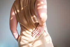 Le donne sono dolore alla schiena Supporto usato della mano alla vita fotografie stock