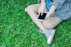 Le donne sta giocando il telefono cellulare Immagine Stock