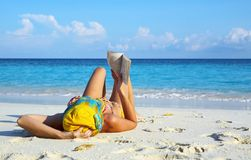 Le donne sta leggendo su una spiaggia Fotografie Stock Libere da Diritti