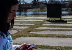 Le donne sta tenendo un telefono contro lo sfondo del fiume Immagini Stock