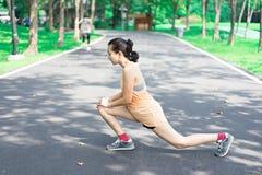 Le donne stanno allungando prima di pareggiare nel parco immagini stock libere da diritti