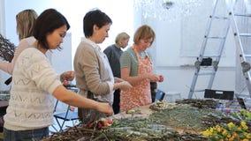 Le donne stanno lavorando con i fiori che creano le composizioni floristiche archivi video