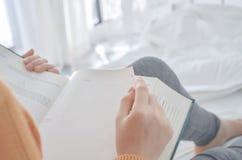 Le donne stanno leggendo un libro che tiene un vetro nero fotografie stock