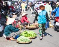 Le donne stanno vendendo i verdi alla via ammucchiata del mercato fotografia stock