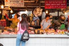 Le donne stanno vendendo la carne al mercato bagnato immagine stock