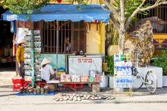 Le donne stanno vendendo le cose sulla via della città antica di Hoi An fotografia stock libera da diritti