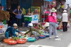 Le donne stanno vendendo le verdure al mercato bagnato immagine stock