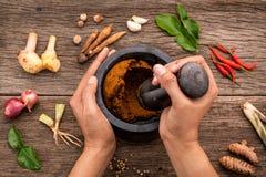 Le donne tengono il pestello con il ingr rosso della pasta di curry della spezia e del mortaio Immagine Stock