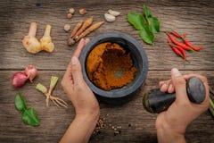 Le donne tengono il pestello con il ingr rosso della pasta di curry della spezia e del mortaio Fotografia Stock Libera da Diritti