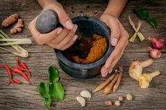Le donne tengono il pestello con il ingr rosso della pasta di curry della spezia e del mortaio Immagini Stock Libere da Diritti