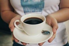 Le donne tengono una tazza di caffè nero Tono d'annata Immagini Stock