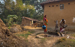 Le donne tribali ricava l'acqua da un pozzo artesiano profondo ad un villaggio indiano rurale Immagini Stock