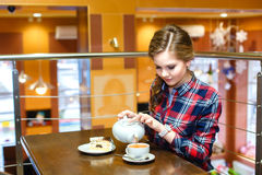 Le donne in una camicia di plaid versa il tè verde Fotografia Stock