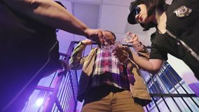Le donne in uniformi della polizia versano l'alcool ad un prigioniero senza tetto in una cella di prigione archivi video