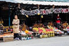 Le donne vendono la caramella della frutta e la frutta lungo la strada immagini stock libere da diritti
