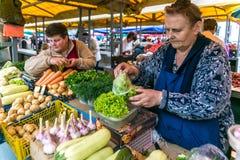 Le donne vendono sulle verdure mature del mercato, cipolle, peperoni, cetriolo, verdi Immagini Stock