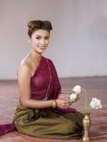 Le donne vestite in Tailandia antica tradizionale stanno piegando i fiori di loto immagine stock libera da diritti