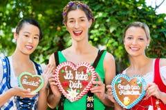 Le donne in vestiti bavaresi tradizionali dentro beergarden Fotografie Stock