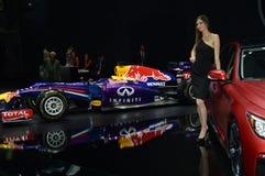 Le donne in vestito nero da Infiniti team vicino all'automobile Red Bull ed al salone internazionale dell'automobile di Mosca del Immagini Stock Libere da Diritti