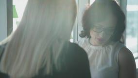 Le donne in vetri stanno e con attenzione esaminano i documenti video d archivio
