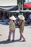 Le donne vietnamite in cappello conico tradizionale vendono i biglietti di lotteria sulle vie di Nha Trang fotografia stock