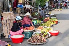 Le donne vietnamite stanno vendendo i frutti al mercato bagnato immagini stock libere da diritti