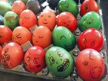 Le dos allumé a coloré des oeufs de pâques avec les visages drôles Images stock